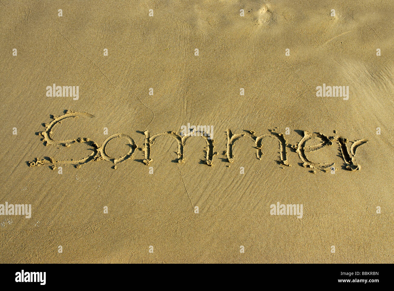 'Sommer', summer written in the sand - Stock Image