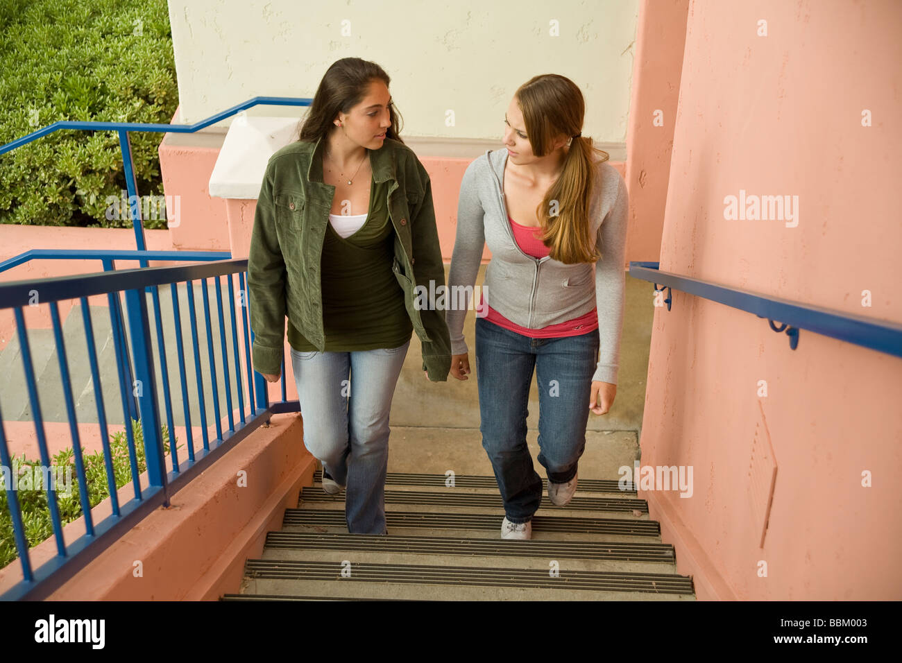young person people 15 16 17 year old Hang hanging out two Racially mixed mix Ethnic diversity teen girls take stairs - Stock Image