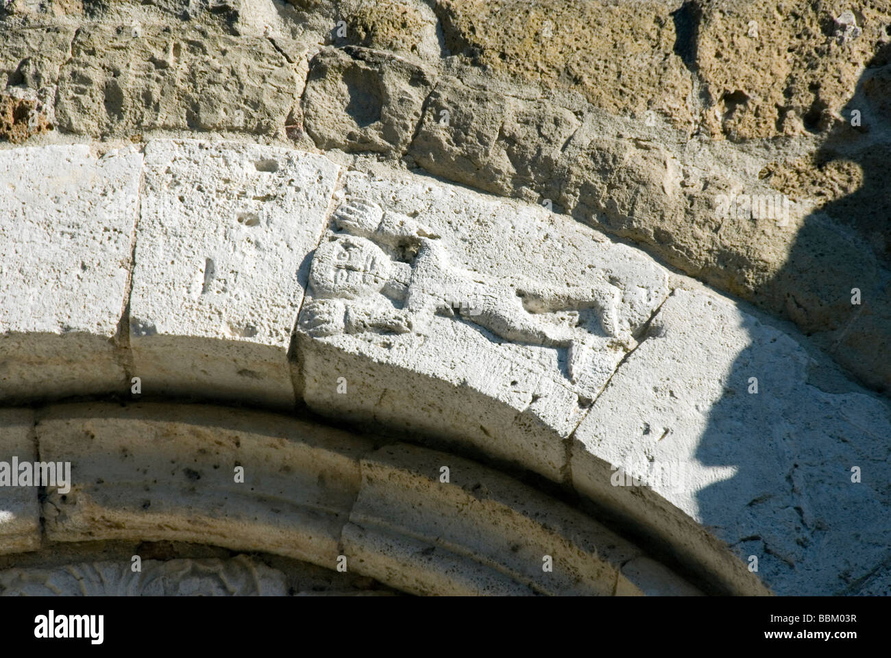 figure of a man carved in travetine on an arch of the Cathedral of Sovana and birthplace of Pope Gregory VII - Stock Image