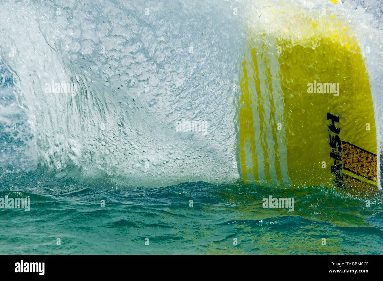 The splash of water generated by a sliding sailboard of a windsurfer - Stock Image