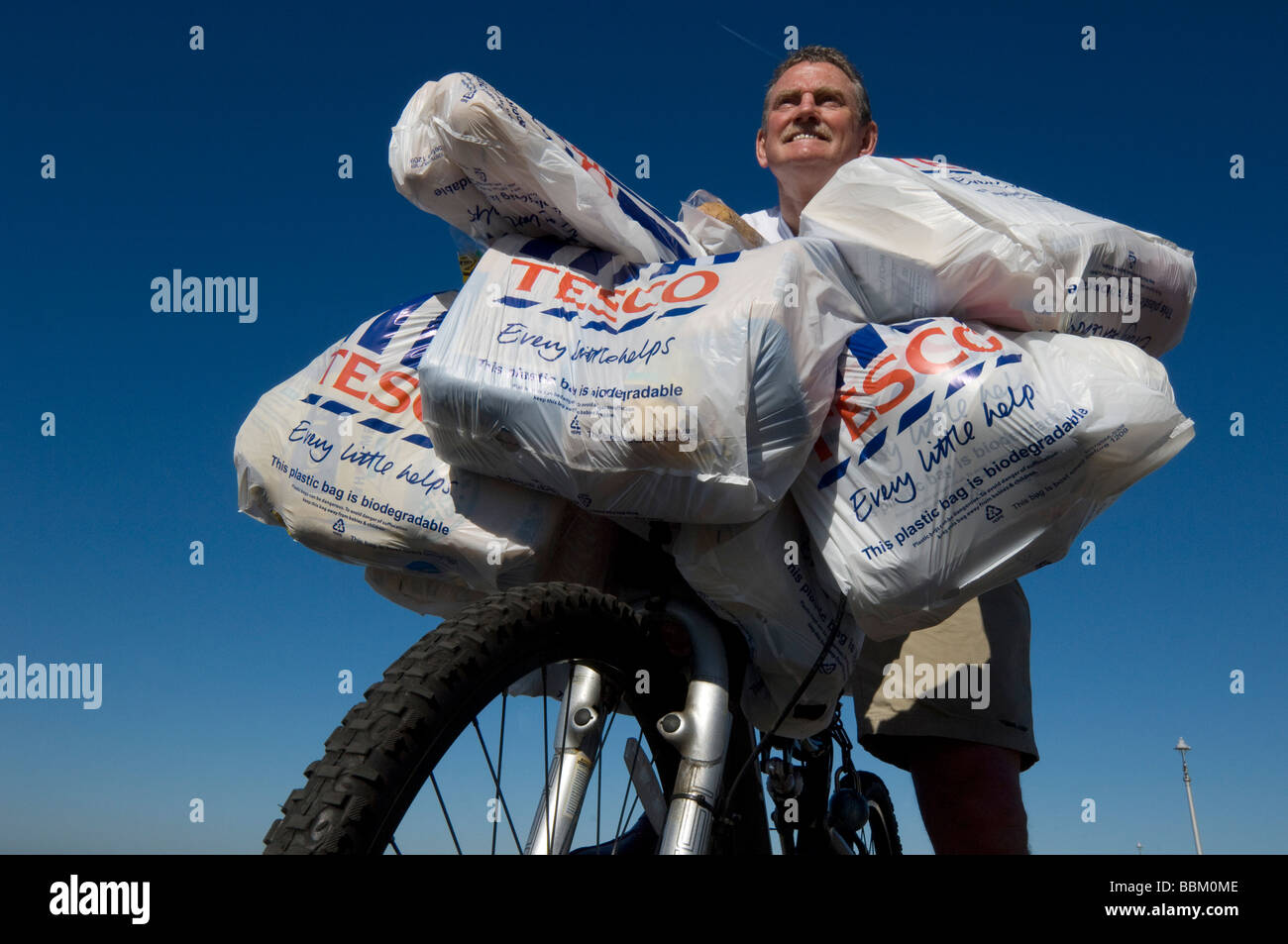A man coming back from shopping at Tesco on a bike with laden with plastic bags full of groceries. - Stock Image