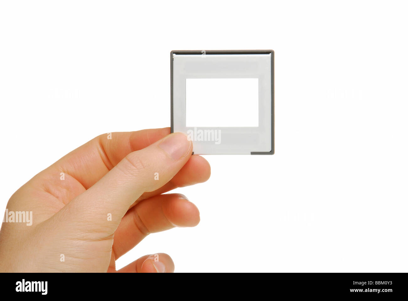 Female hand with slide frame, symbolic a presentation - Stock Image