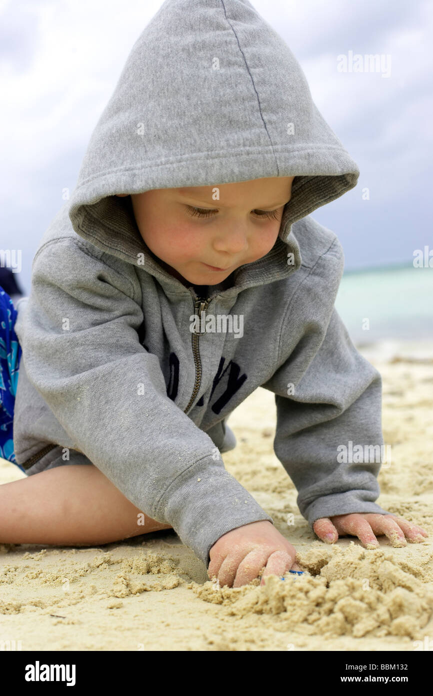 Boy playing in sand on the beach, Camagüey, Cuba - Stock Image
