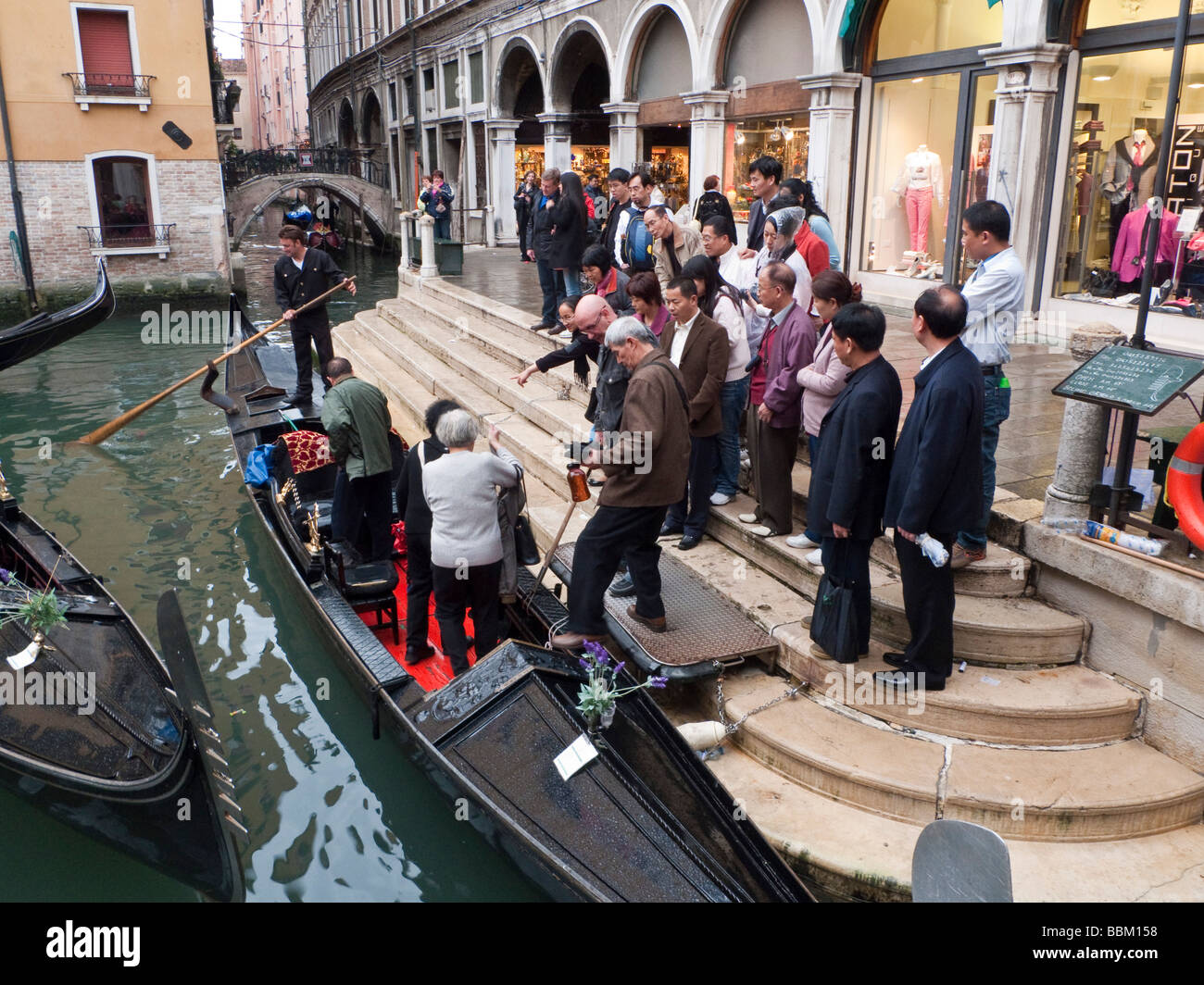 Group of tourists boarding a gondola at Bacino Orseolo San Marco Venice Italy - Stock Image