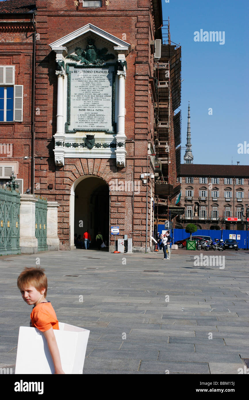 A kid walking in the Turin downtown. Piazza Castello. Mole Antonelliana in the background. - Stock Image