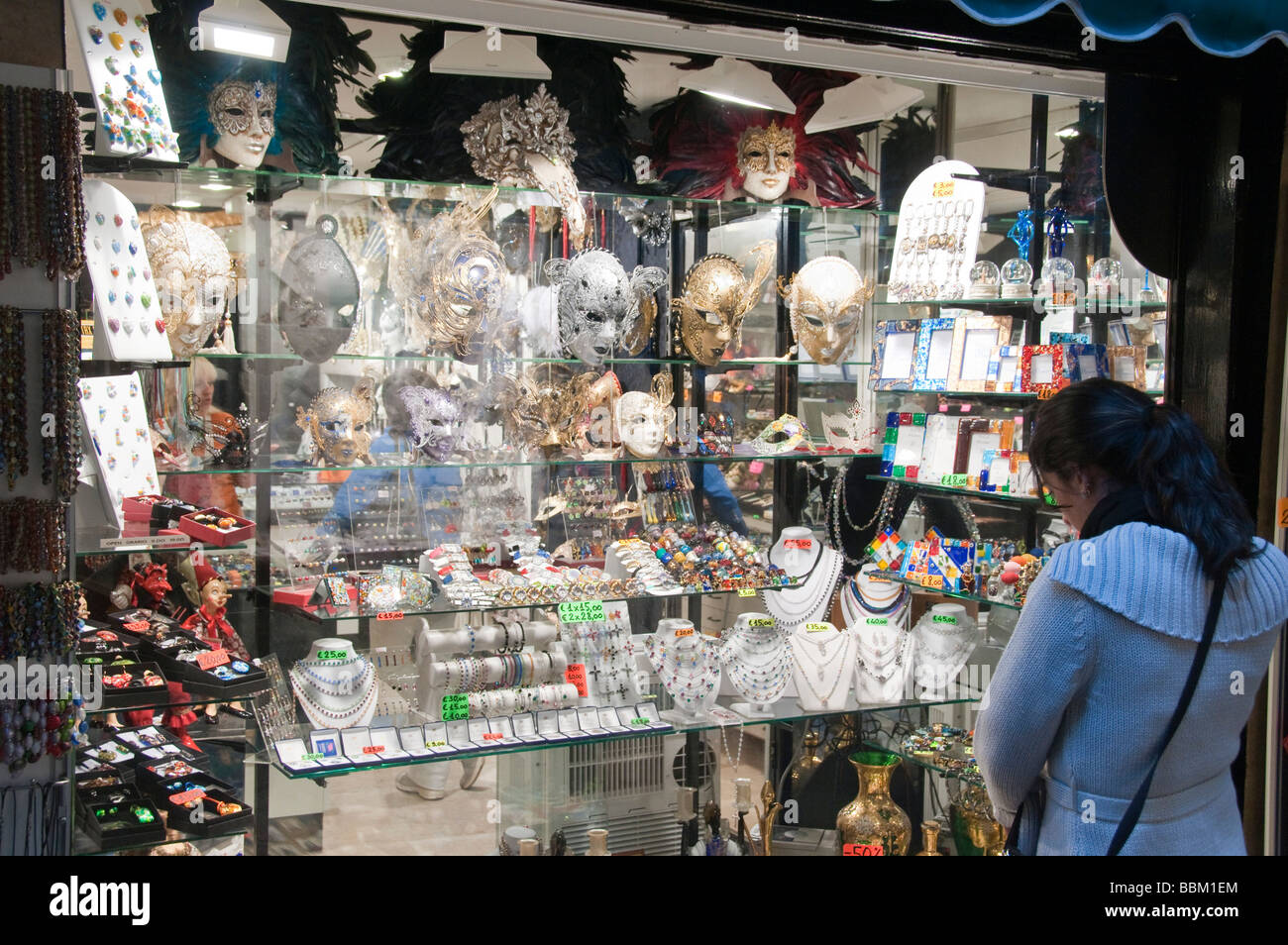 Tourist looking at face masks on display in shop window Murano Venice Italy - Stock Image