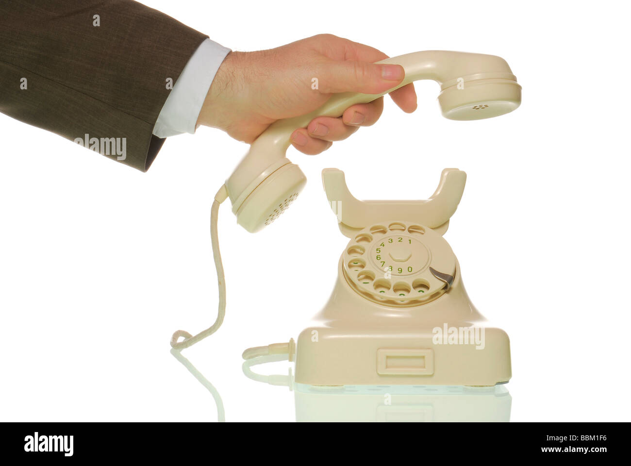 Business man reaching for old-fashioned telephone - Stock Image