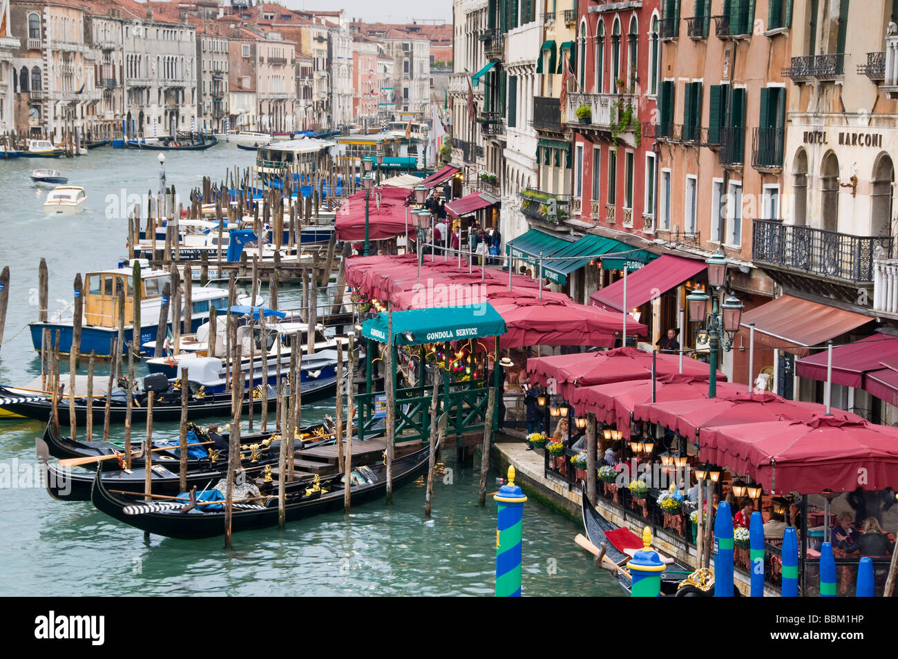 Restaurant seating and gondola moorings on the Grand Canal Riva del Vin Venice Italy - Stock Image