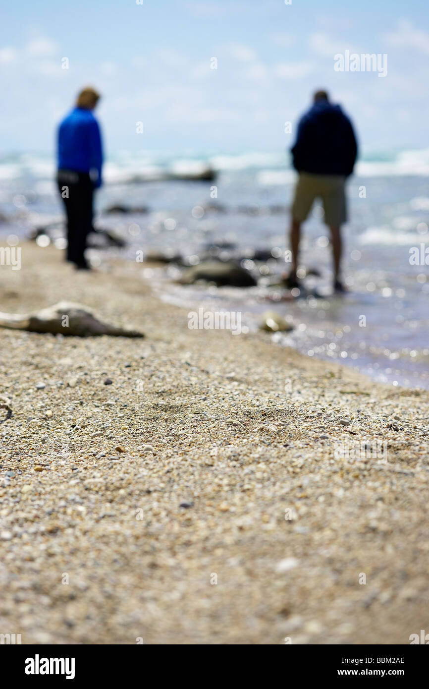 Out of focus couple on beach shoreline, Ontario - Stock Image