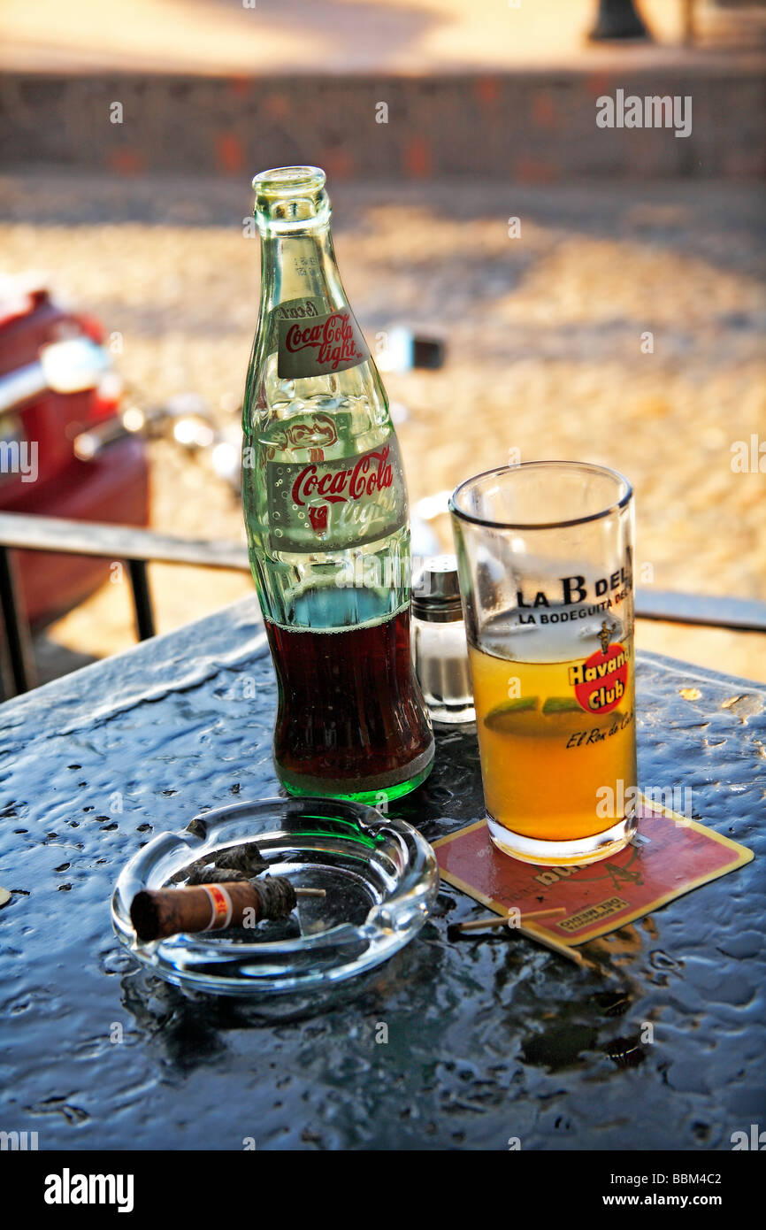 Still life setting coca cola bottle rum glass and cigar on table in bar at Puerto Vallarta Mexico - Stock Image