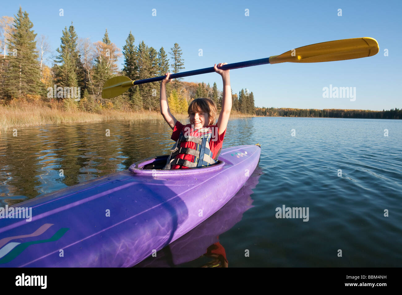 Smiling 10 year old boy holding paddle above kayak, Lake Katherine, Riding Mountain National Park, Manitoba - Stock Image