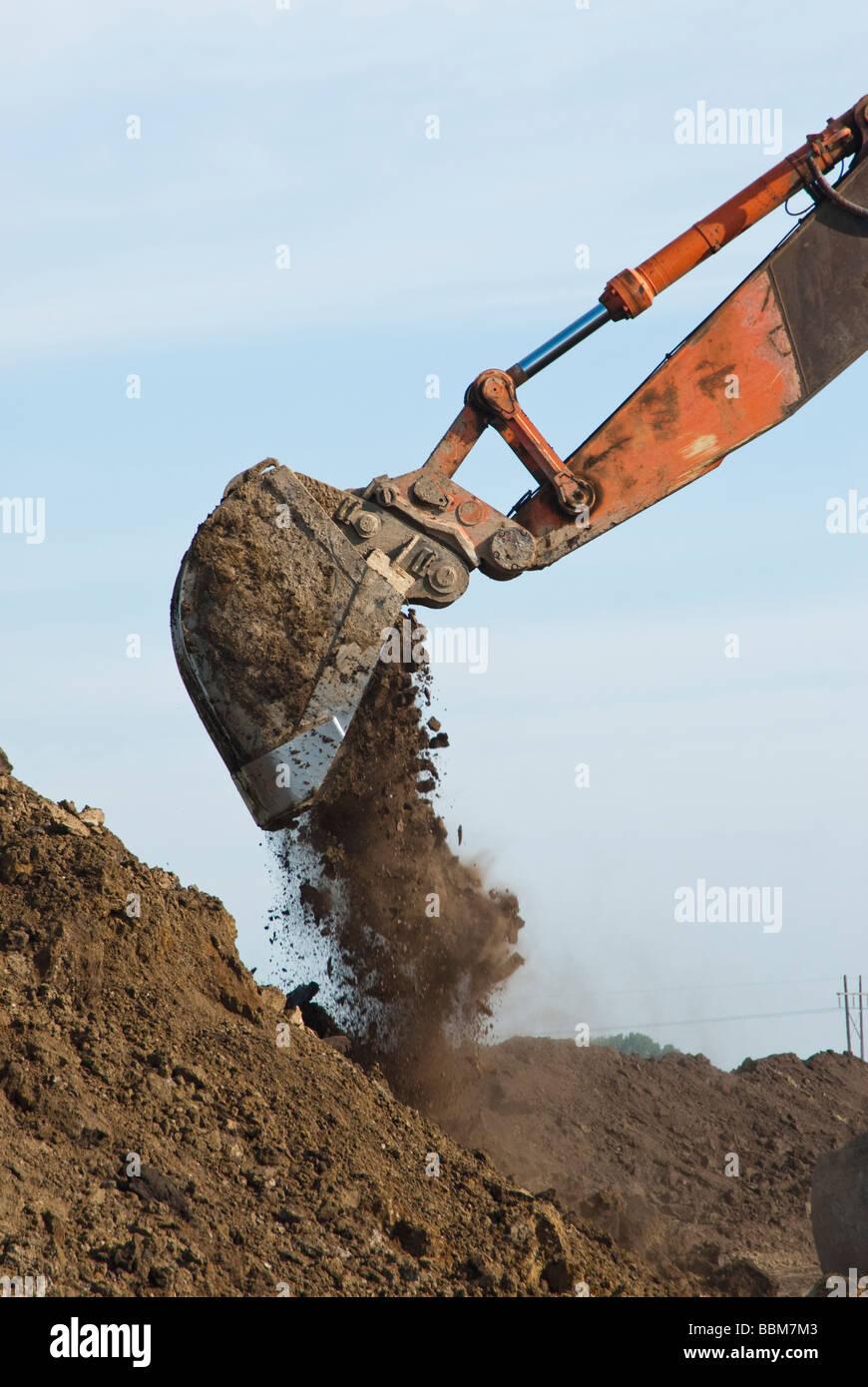 an excavator dumping a bucket of dirt - Stock Image