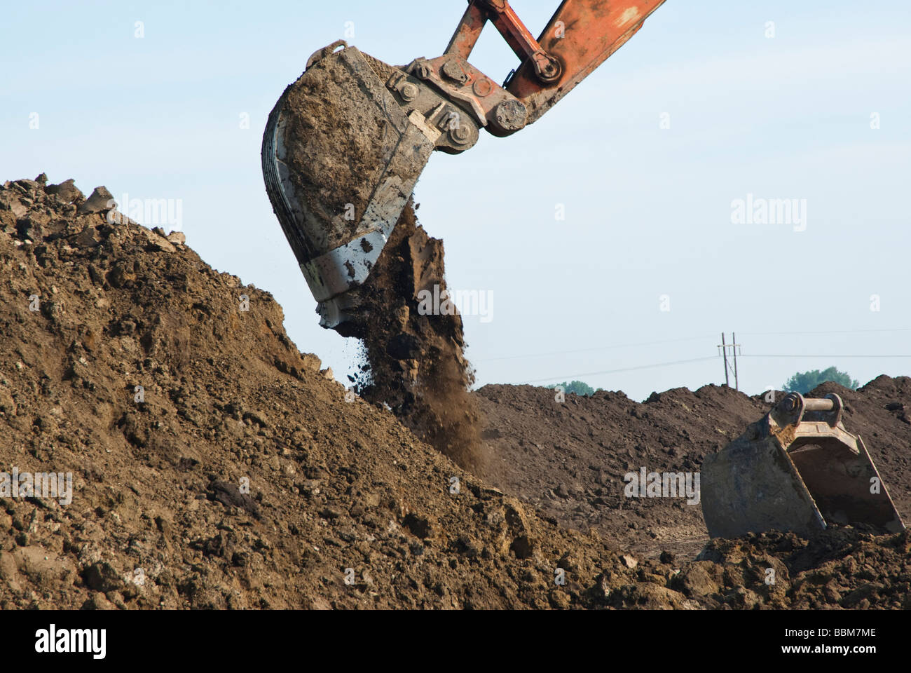 an excavator dumping a bucket of dirt - Stock Image