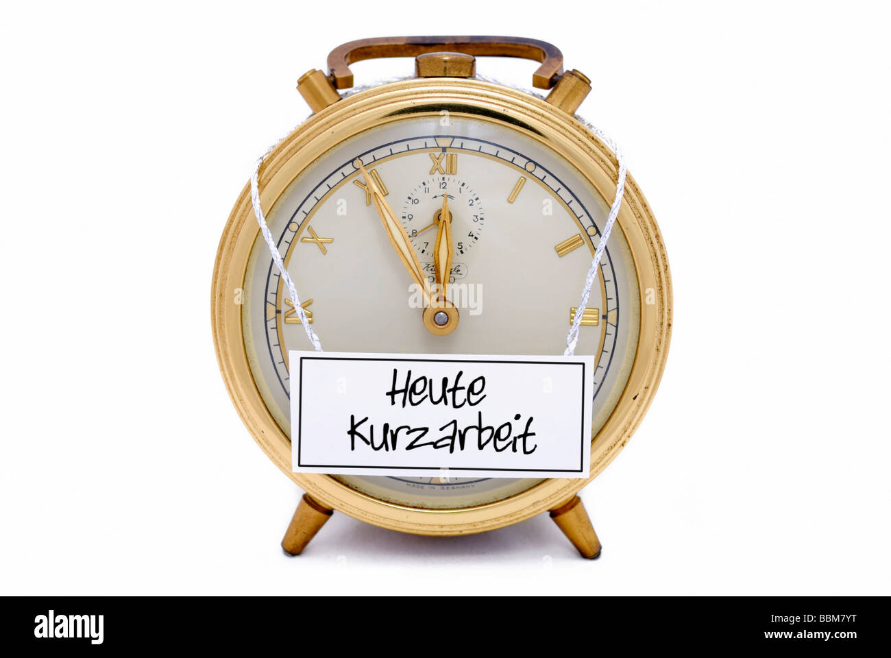 Alarm clock, 5 to 12, 'Heute Kurzarbeit', German for: today short-time work, written on a sign - Stock Image