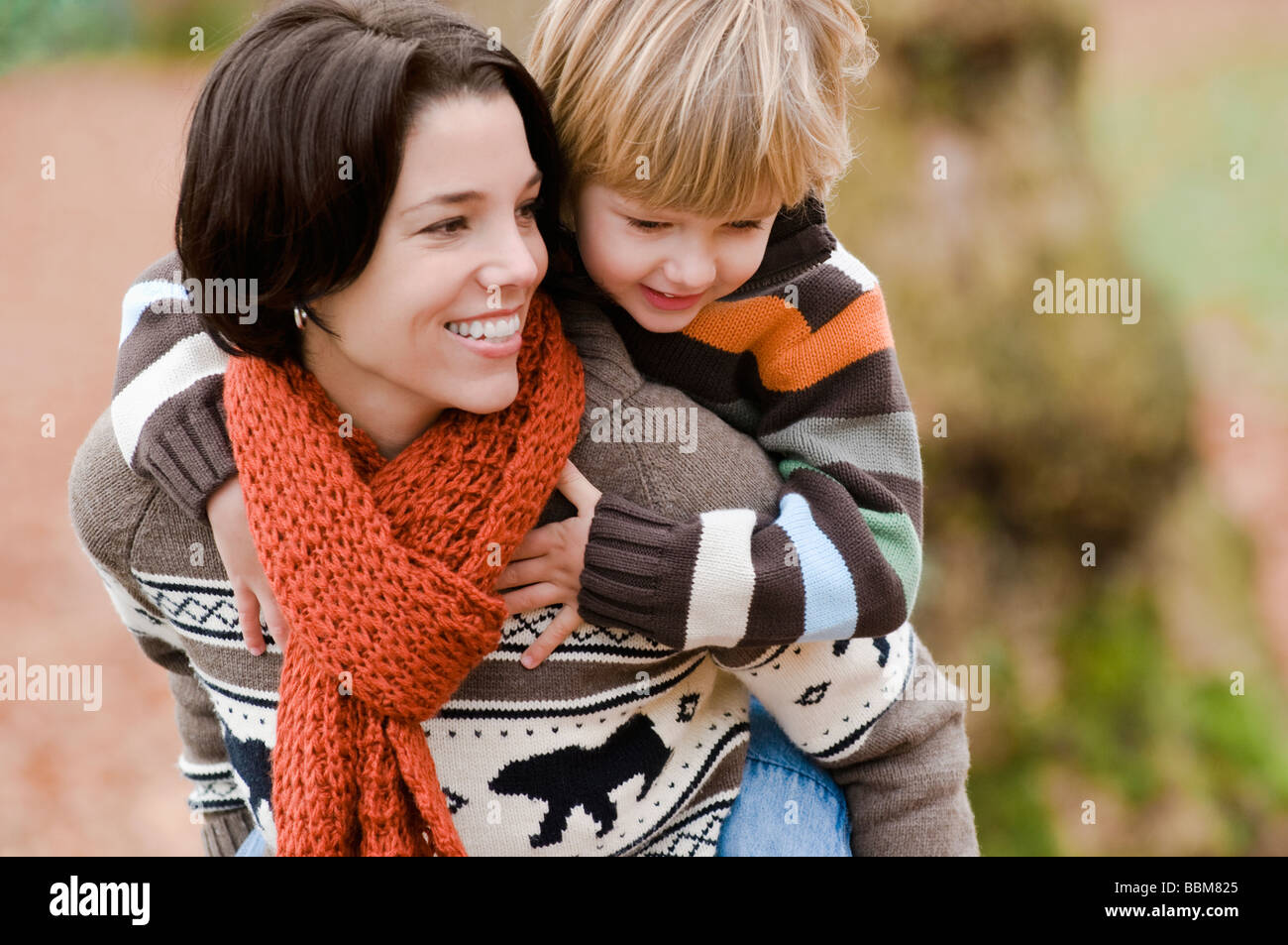 Young boy rides piggy back on woman's back in autumn, Vancouver, British Columbia - Stock Image