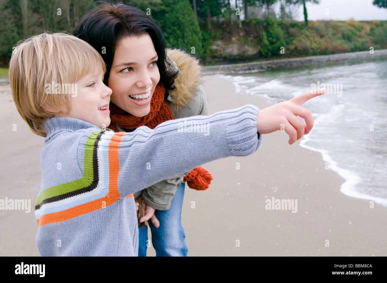 Young boy with mother points toward ocean, Vancouver, British Columbia - Stock Image
