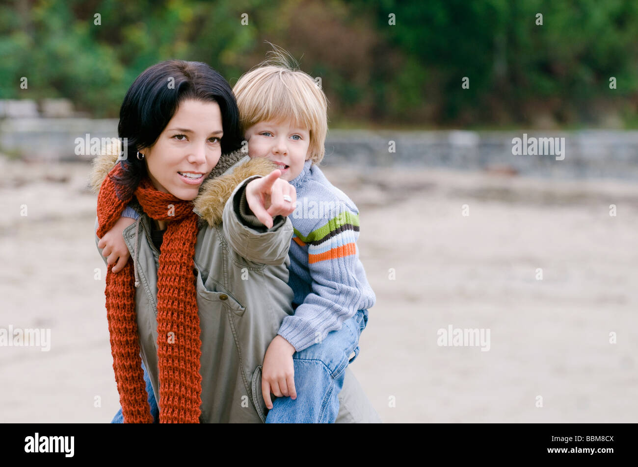 Son looks as mom points out something on the beach, Vancouver, British Columbia - Stock Image