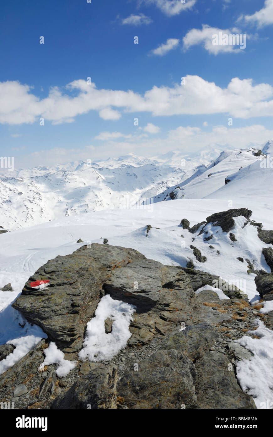Marker of a ski tour route on metamorphic primitive rocks with footprints in the snow, Zillertal main crest at back, - Stock Image