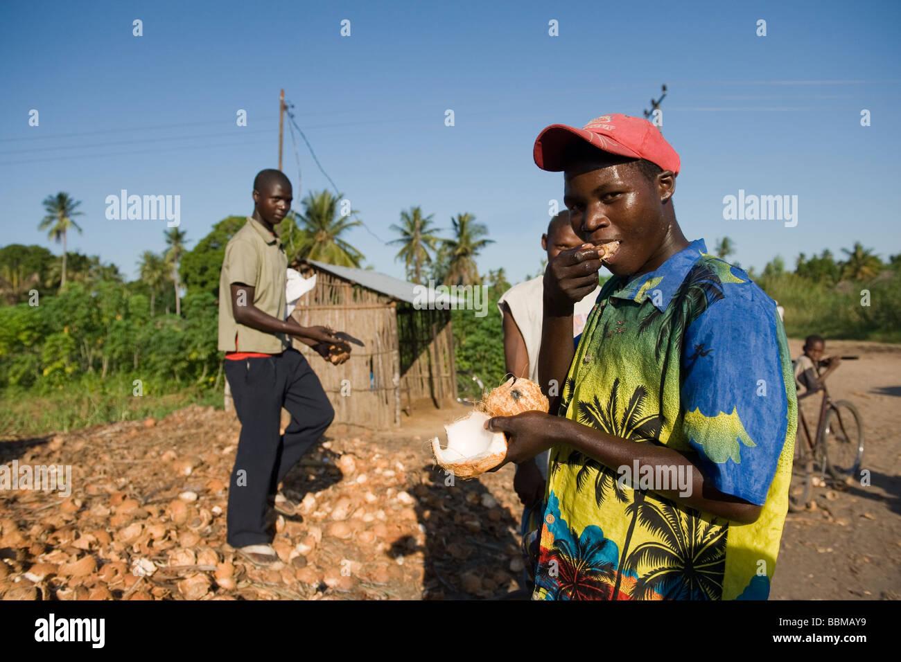 A man eats a fresh coconut Quelimane Mozambique - Stock Image