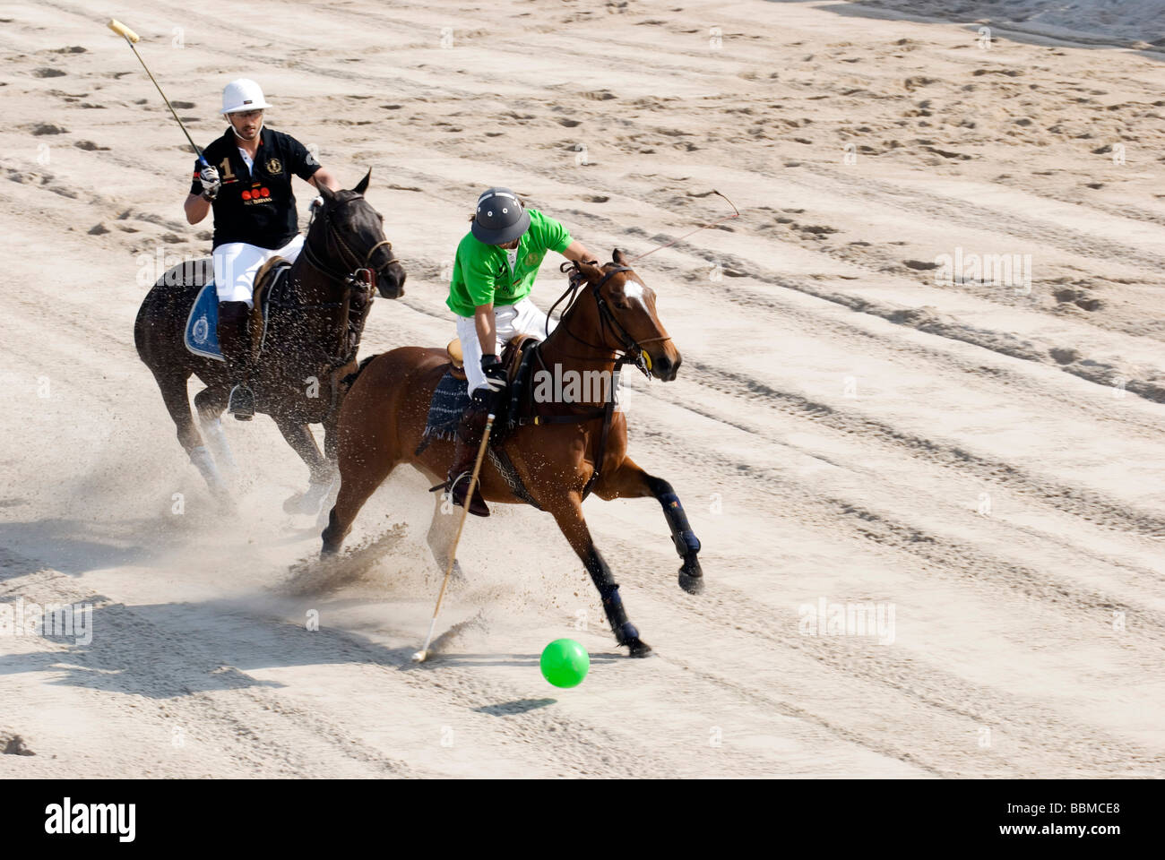 Game scene with Christobal Durrieu, green, black helmet, during beach polo tournament, Timmendorfer Strand, Schleswig - Stock Image