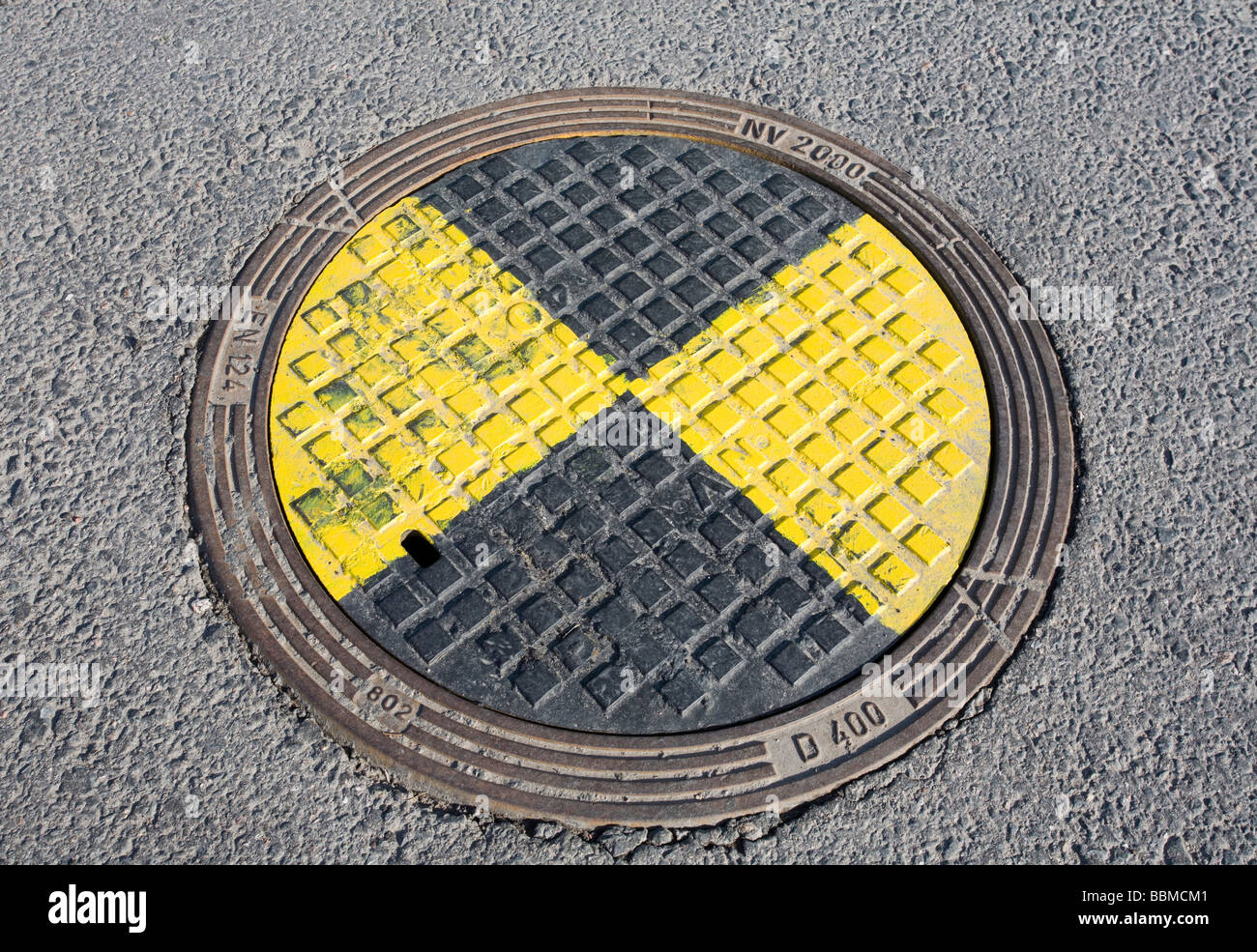 man hole sewer cover painted yellow and black - Stock Image