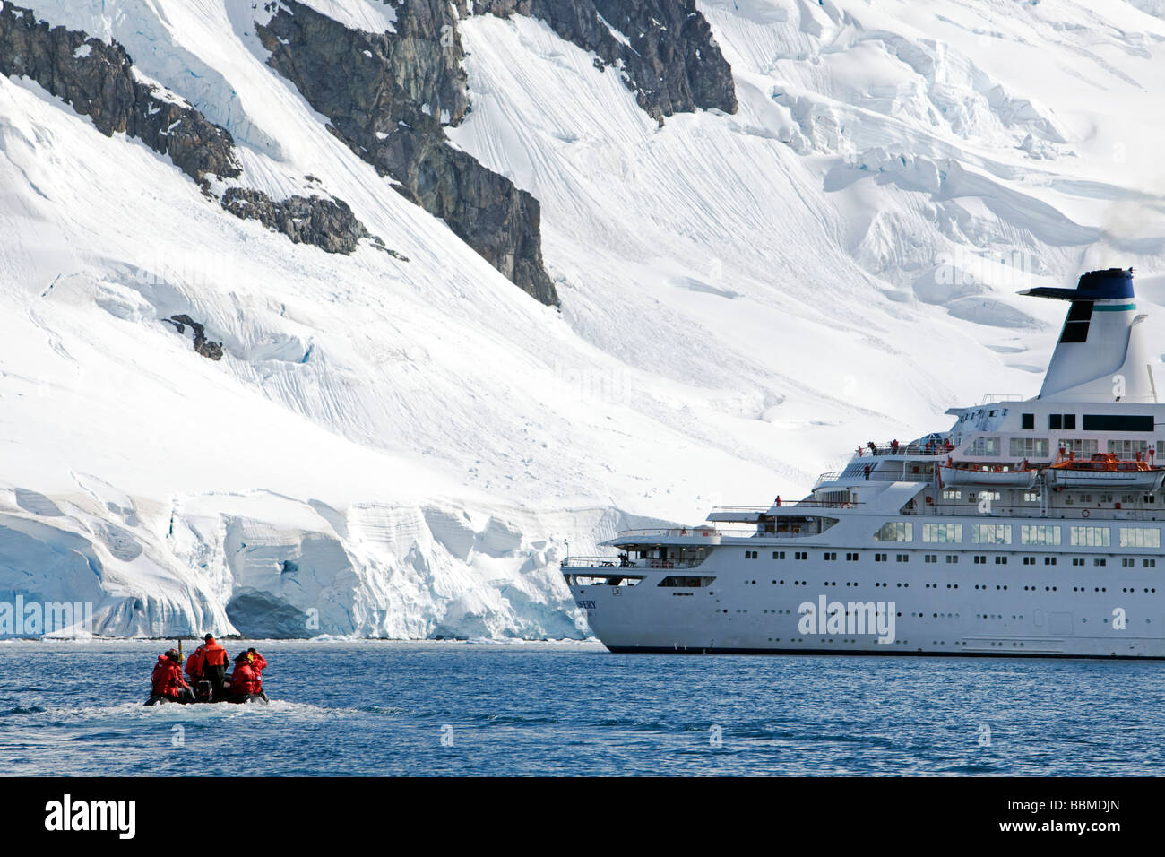 Antarctica, Antarctic Peninsula.   A zodaic with passengers returns to an expedition cruise ship anchored in Paradise - Stock Image