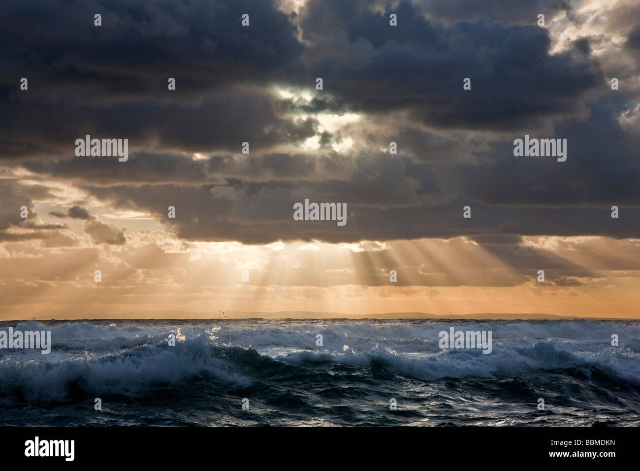 Australia, Victoria.  In the late afternoon, the  sun breaks through threatening clouds over the Bass Straits. - Stock Image