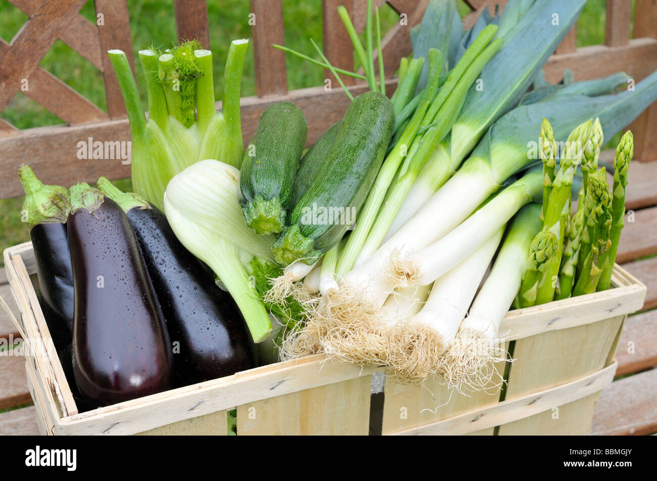 Green asparagus, eggplants, zucchini, spring onions, fennel, leeks in a basket Stock Photo