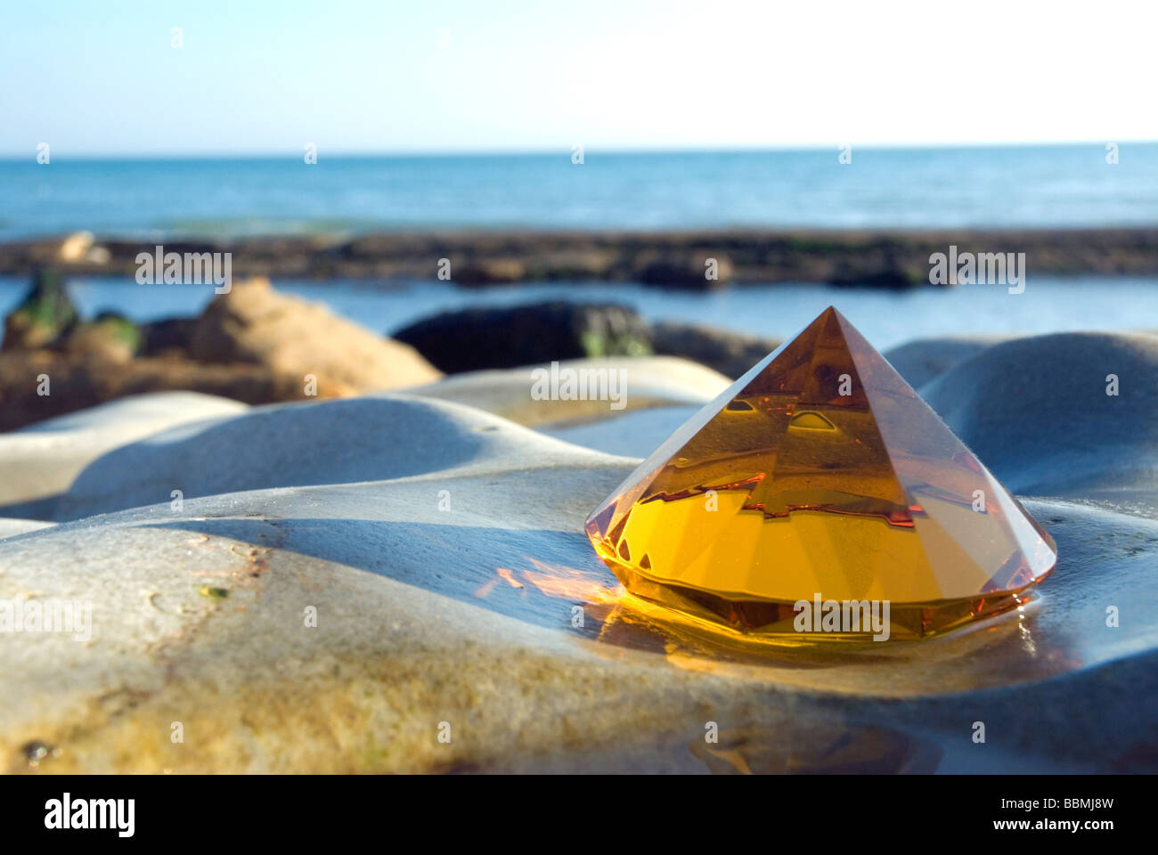 Amber glass pyramid on rock with seawater pool - Stock Image