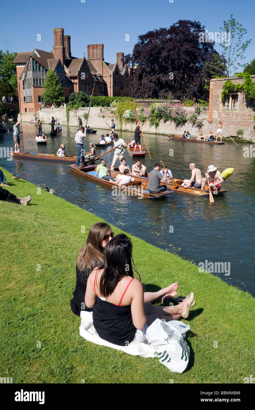 People sitting on the banks of the River Cam at Clare College, Cambridge, watching the punting on a summers day - Stock Image