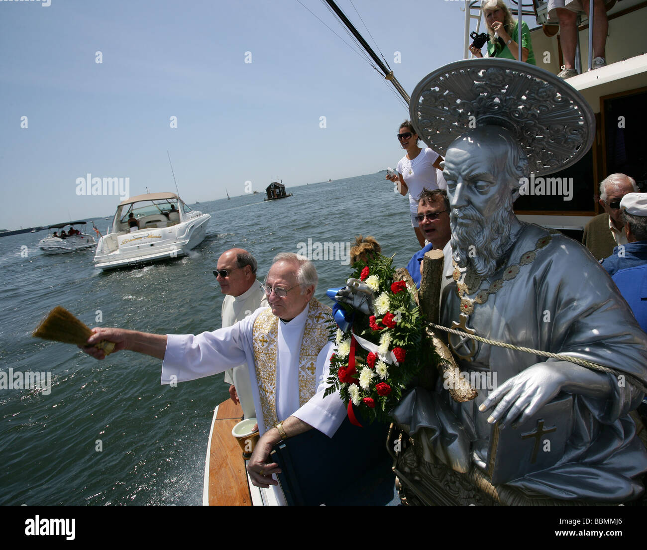 A Priest blesses boats during the annual St. Andrew the Apostle Society blessing of the fleet in New Haven Connecticut - Stock Image