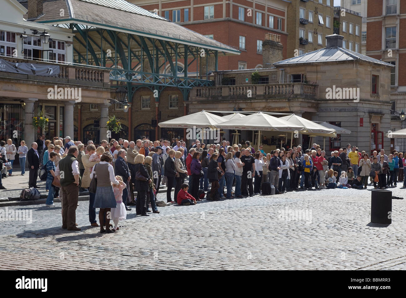 a small crowd looks on at a performer at Covent Garden in London - Stock Image