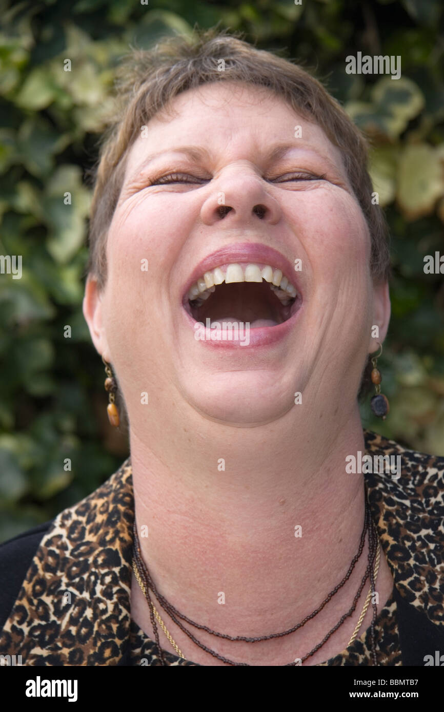 A woman with her head leaning back laughing uncontrollably - Stock Image