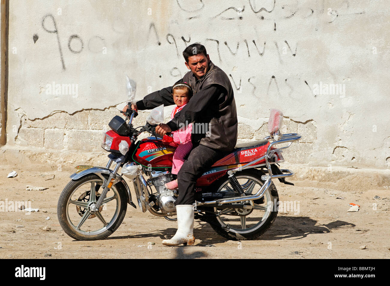 Man with child on motorbike in Aleppo, Syria, Asia - Stock Image