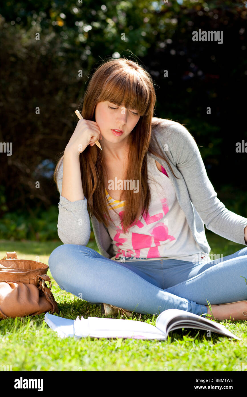 Girl with books outside on grass - Stock Image
