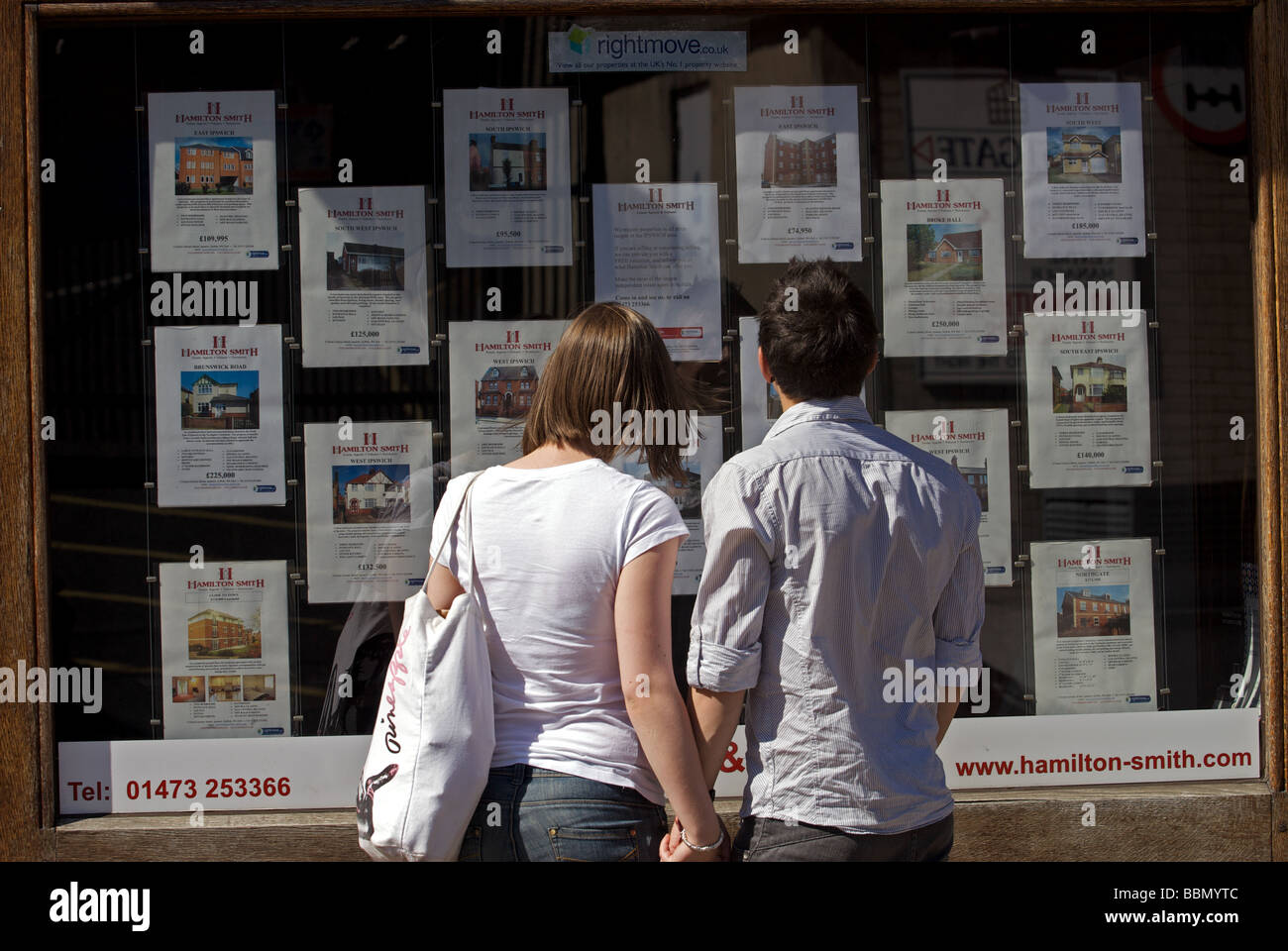 Young couple looking at houses for sale in an estate agents window - Stock Image