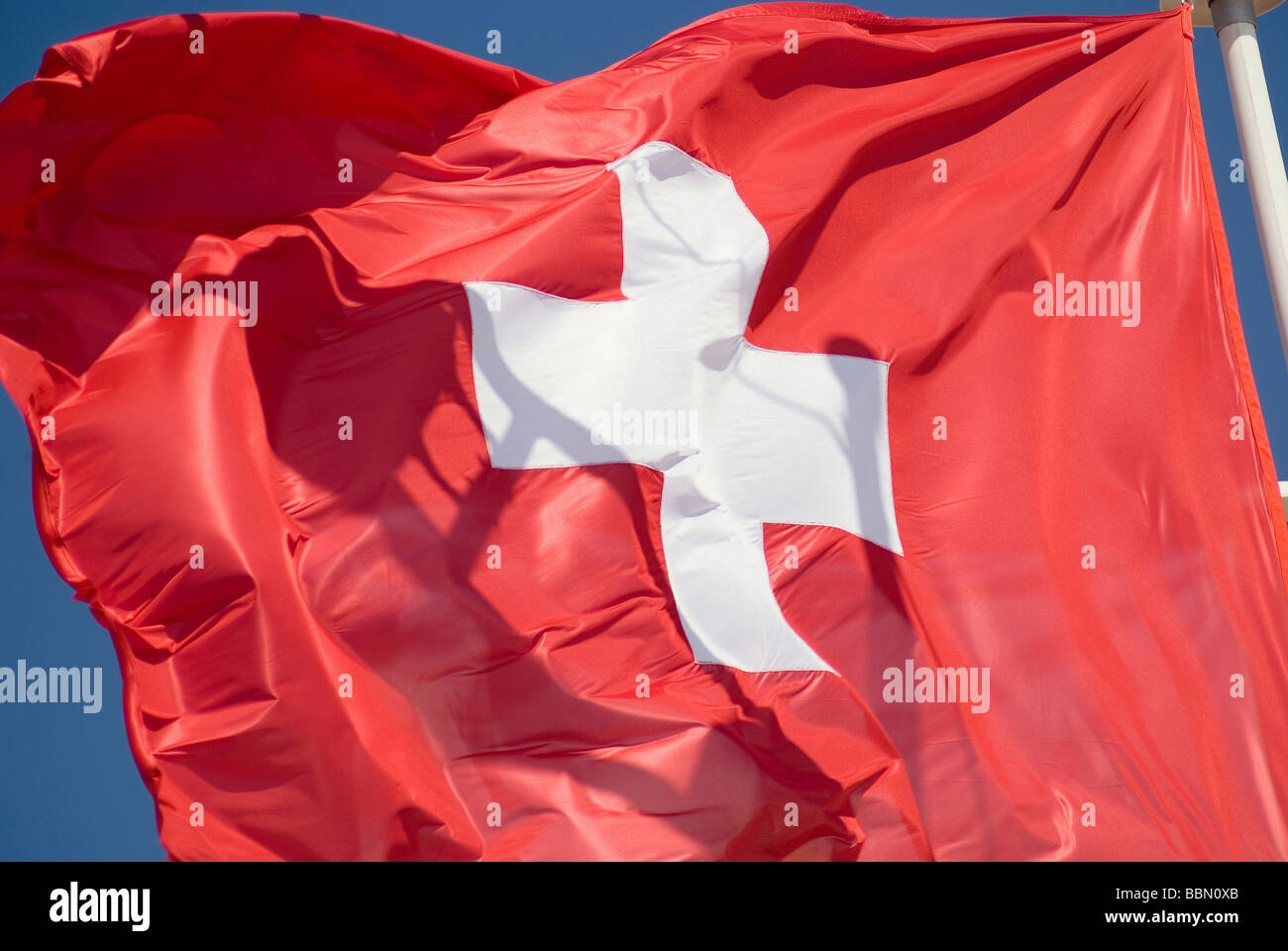 Swiss national flag fluttering in the wind - Stock Image