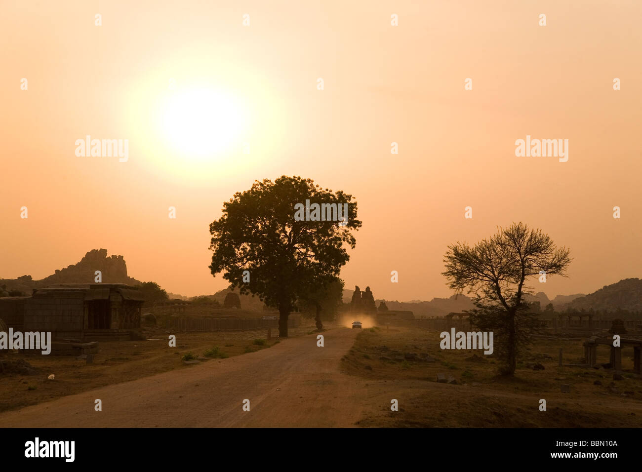Sunset over a dusty road which runs towards the Vittala (Vitthala) Temple in Hampi, India. - Stock Image