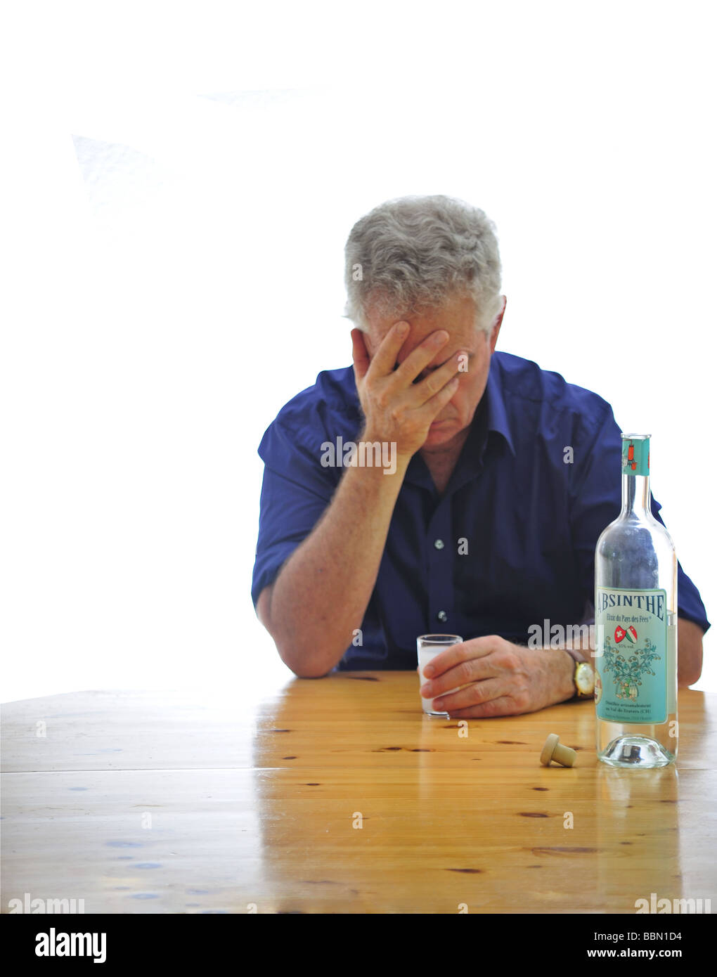 A figure out of focus sits at a table holding a glass of absinthe. Focus on the absinthe bottle. Isolated on white - Stock Image