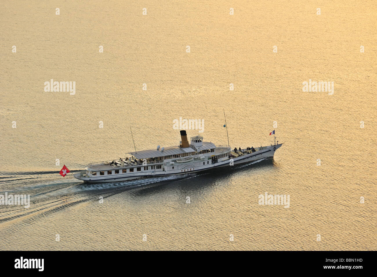 The Swiss paddle steamer 'Vevey' on Lac Leman in the evening. Space for text on the water. - Stock Image
