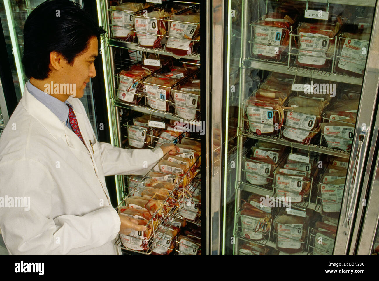 Technician pulling supply from refrigerated blood bank storage - Stock Image