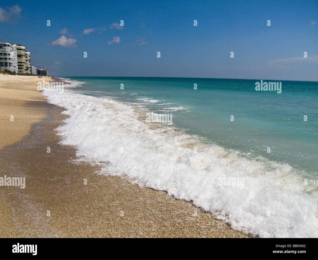 small waves wash up on shore at beach - Stock Image