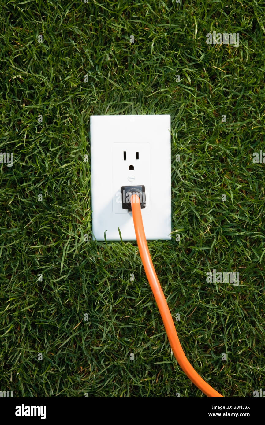 Electrical outlet in grass with extension cord plugged in Stock Photo