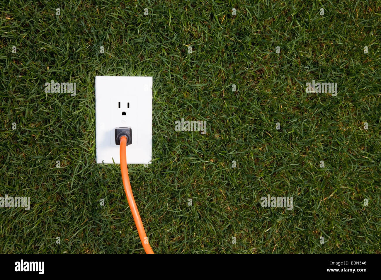 Electrical outlet in grass with extension cord plugged in - Stock Image
