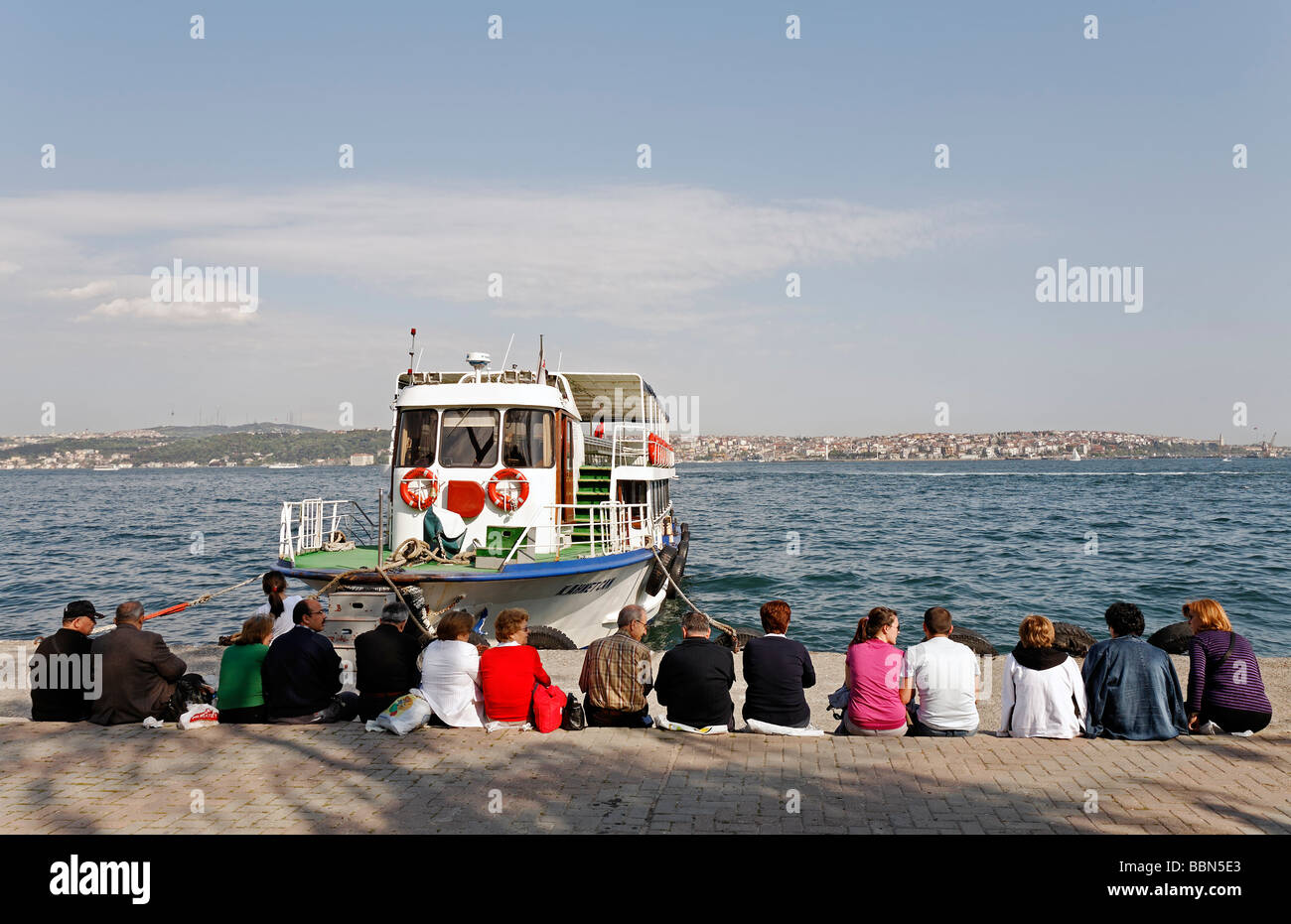 People sit in a row on the quay, waiting for the ferry, Bosphorus panorama, Kabatas, Istanbul, Turkey Stock Photo