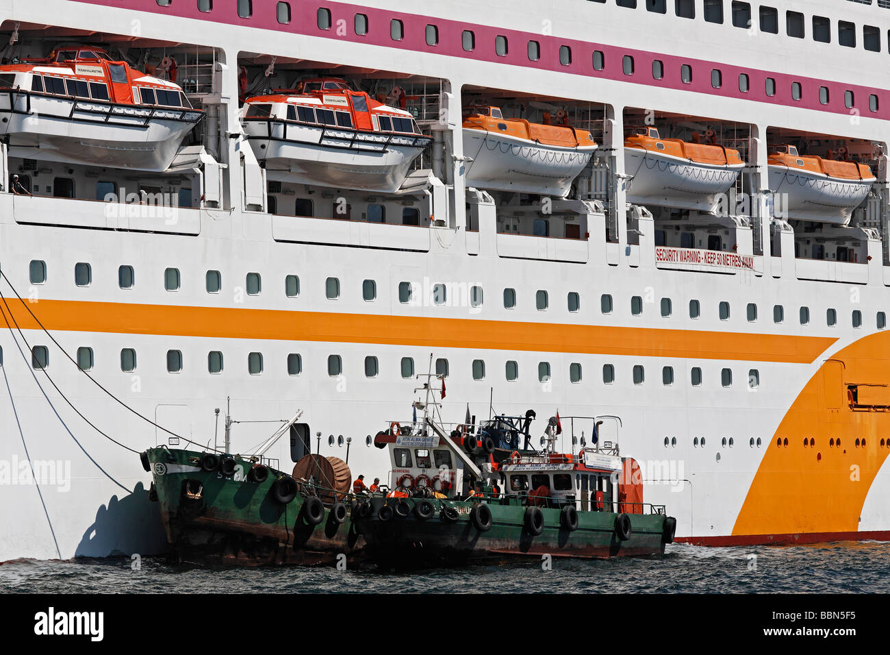 Ship's side of the cruise ship Celebrity Solisitce, lifeboats in the lower decks, boats takes waste off board, - Stock Image