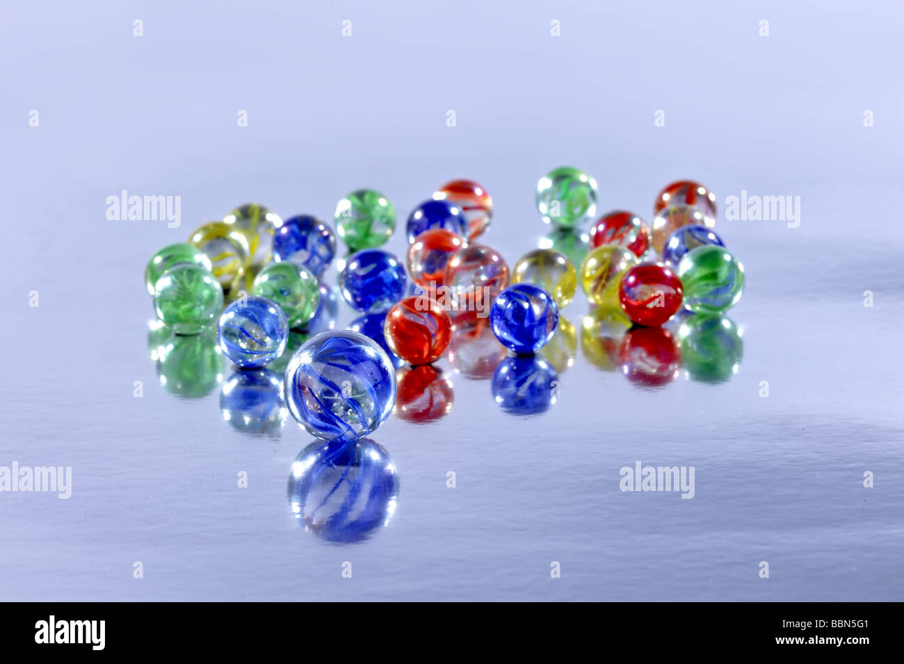 Many colourful marbles on a reflective surface for a background use - Stock Image