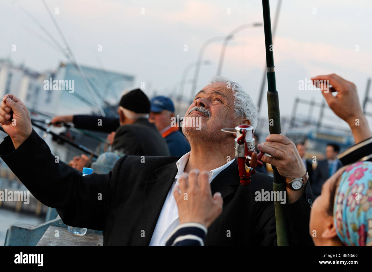 White haired Turkish angler examines his catch, Galata Bridge, Eminoenue, Istanbul, Turkey - Stock Image