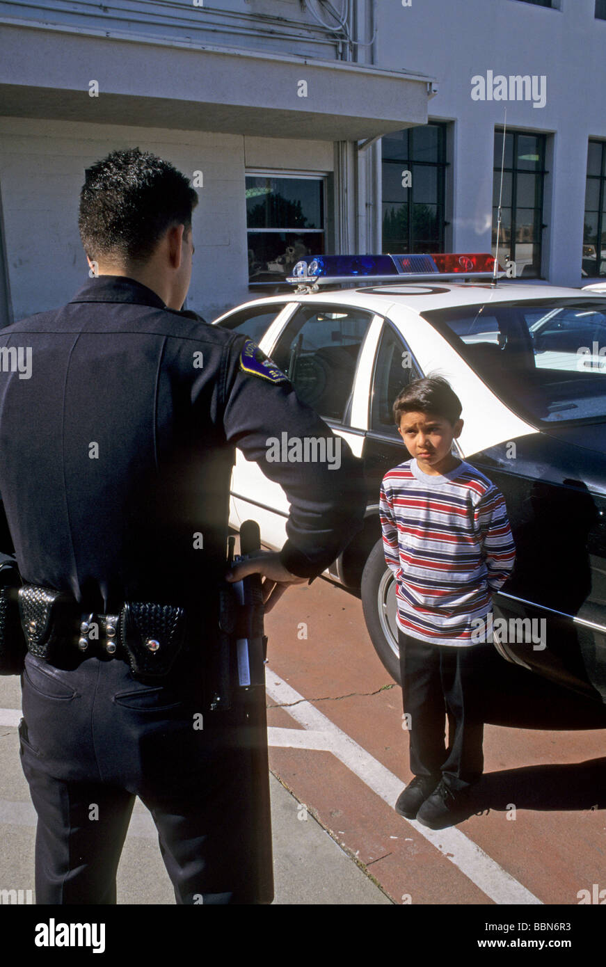 police boy scold trouble scare attention obey bad law legal cop government protect serve question care interview - Stock Image