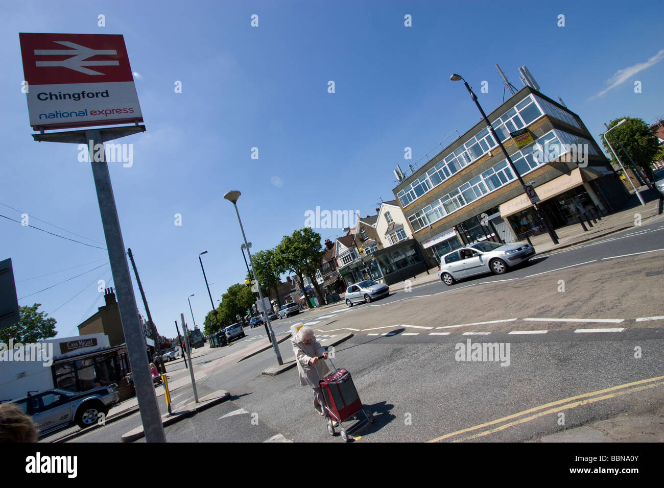 street scene in Chingford London on Essex border with elderly lady pushing trolley, and chingford railway station - Stock Image